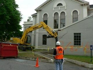 An excavator takes the first bite out of the old courthouse.